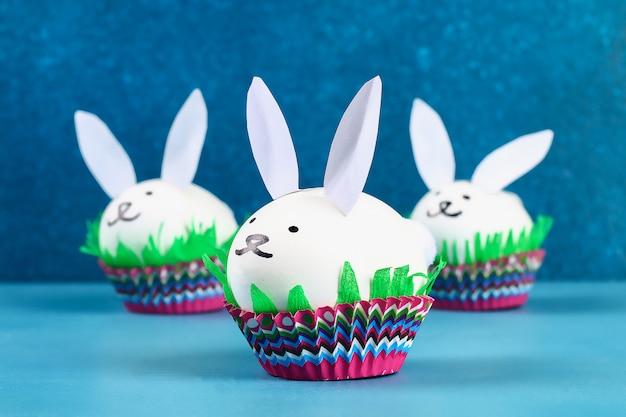 Fai da te il coniglio da uova di pasqua su sfondo blu. idee regalo, decorazioni pasqua, primavera. fatto a mano.