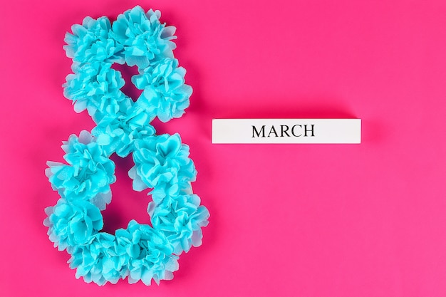 Fai da te otto fatto cartone decorato fiore artificiale fatto carta velina blu tovaglietta rosa sfondo.