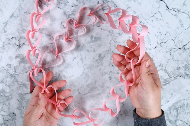 Fai da te. una ghirlanda di cuori per san valentino. decorazioni fai-da-te per il 14 febbraio. vista dall'alto.
