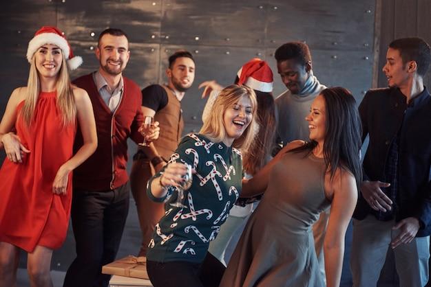 Fai festa con gli amici. loro adorano il natale. il gruppo di giovani allegri che trasportano le stelle filante e le scanalature di champagne che ballano nel nuovo anno fanno festa e che sembrano felici. concetti sullo stile di vita insieme