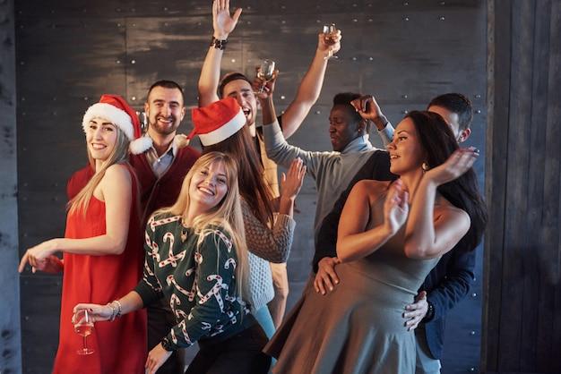 Fai festa con gli amici. loro amano il natale. il gruppo di giovani allegri che trasportano le stelle filante e le scanalature di champagne che ballano nel nuovo anno fanno festa e che sembrano felici. concetti sullo stile di vita insieme