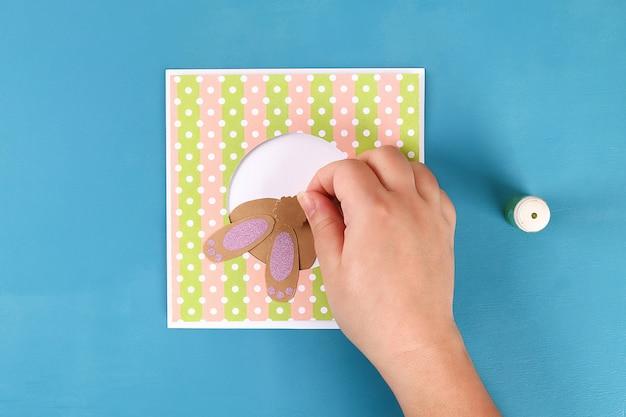 Fai le carte pasquali di carta. auguri di volume con un coniglio, uovo su sfondo blu. 3d.