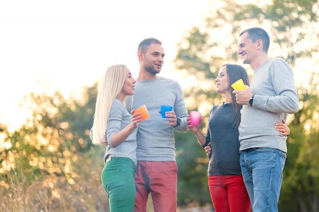 Fai un picnic con gli amici accanto al fuoco. amici della compagnia che hanno un'escursione natura picnic. picnic estivo.