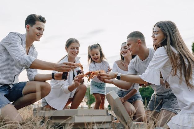 Fai un picnic con gli amici mangiando pizza e bevendo bevande