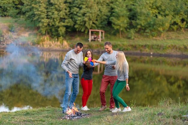 Fai un picnic con gli amici nel lago vicino al falò. amici della società che hanno escursione sul fondo della natura di picnic. escursionisti che si rilassano durante il drink. picnic estivo. divertimento con gli amici