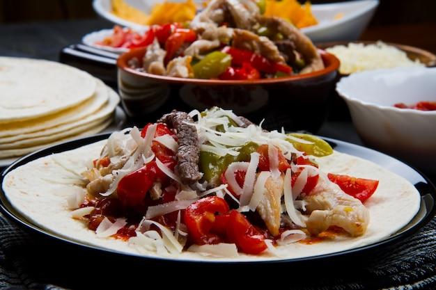 Fajitas di manzo e pollo con peperoni colorati a tortilla