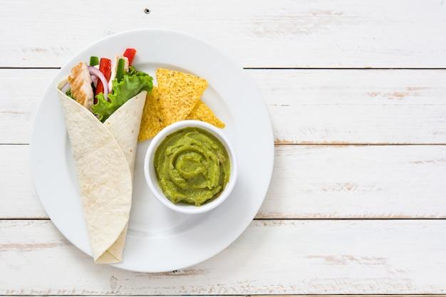 Fajitas di pollo messicano con salsa guacamole su un piatto e un tavolo di legno bianco