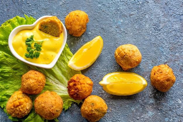 Falafel vegetariano fatto in casa fritto con ceci e broccoli macinati, con salsa al limone e senape