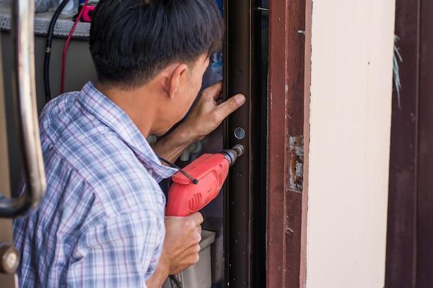 Falegname all'installazione della serratura con il trapano elettrico nella porta di alluminio di legno interna