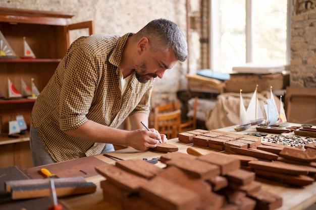 Falegname di legno al lavoro nel suo laboratorio