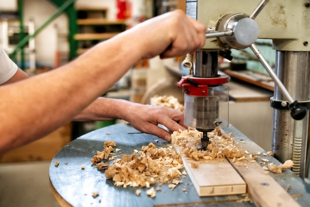 Falegname o carpentiere con un trapano verticale