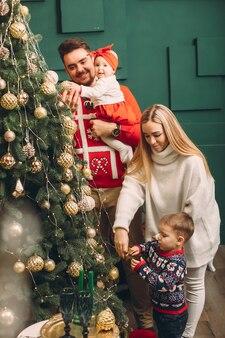 Famiglia a casa vicino all'albero di natale