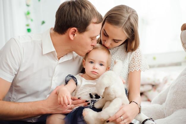 Famiglia adorabile che sorride e che ride, posando alla macchina fotografica