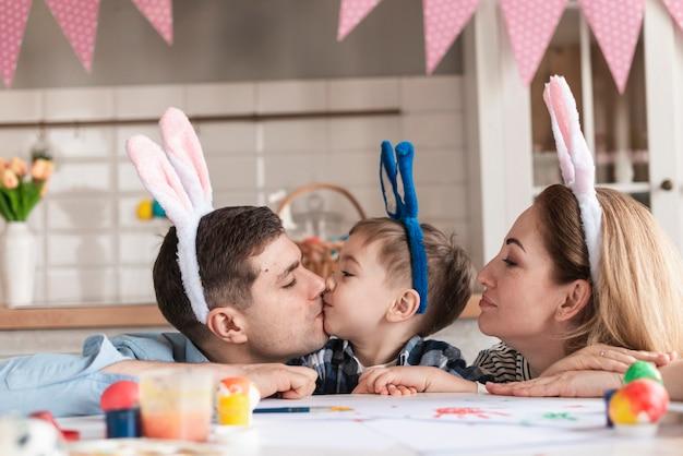 Famiglia adorabile con le orecchie del coniglietto che celebra pasqua