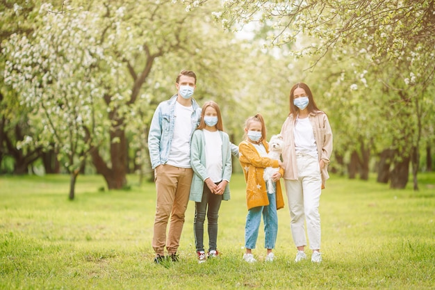 Famiglia adorabile nel giardino di fioritura della ciliegia nelle maschere