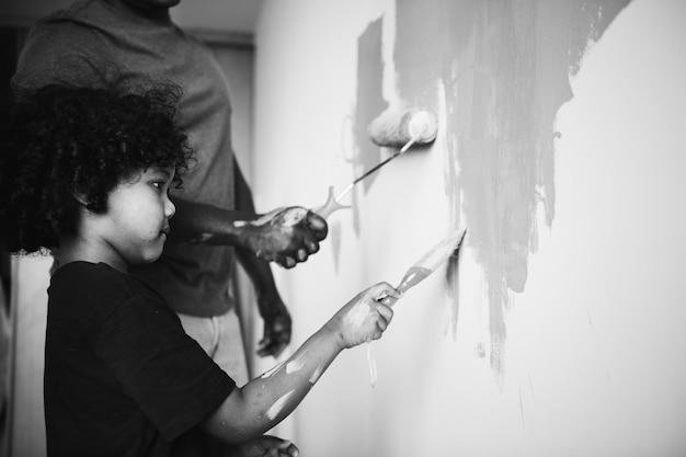 Famiglia africana che dipinge la parete della casa