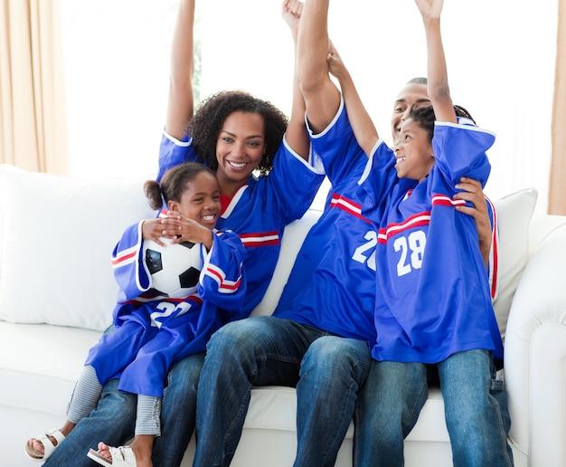 Famiglia afroamericana emozionante che celebra un obiettivo di calcio