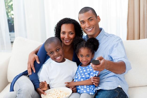 Famiglia afroamericana sorridente che mangia popcorn e che guarda tv