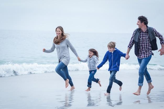 Famiglia allegra che funziona alla riva del mare