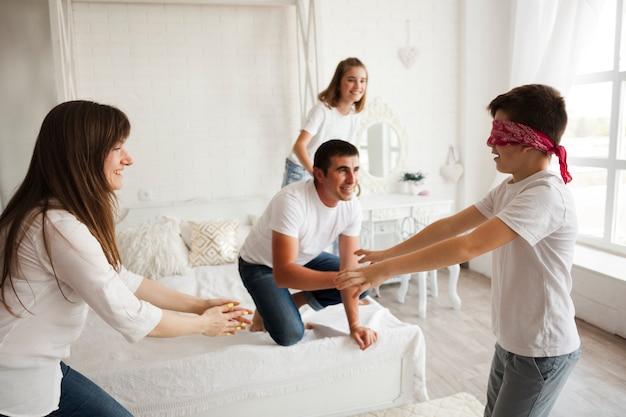 Famiglia allegra che gioca il gioco buff del cieco in camera da letto