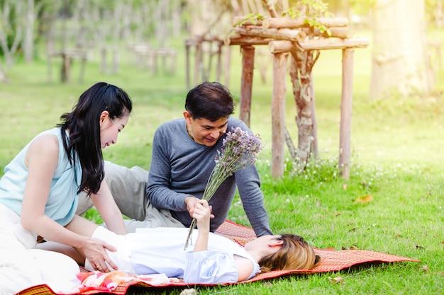 Famiglia allegra che ha picnic che si rilassa insieme sulla natura verde in parco