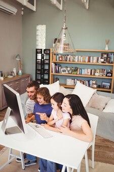 Famiglia allegra che per mezzo del computer a casa