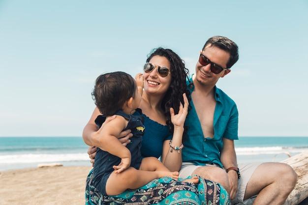 Famiglia allegra che si siede sulla spiaggia