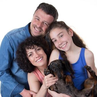 Famiglia allegra con la ragazza e il suo cane isolati