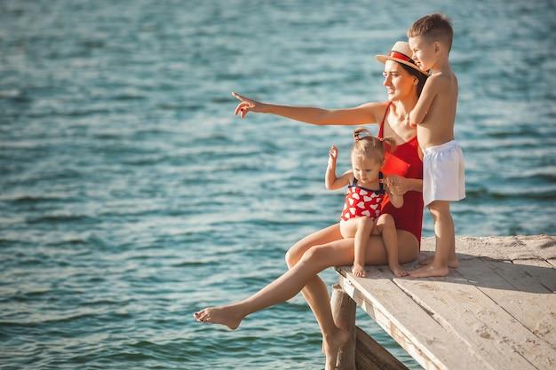 Famiglia allegra felice al molo vicino all'acqua divertendosi. adorabili bambini che giocano con i loro genitori