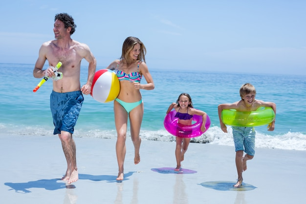Famiglia allegra in esecuzione con attrezzatura da nuoto in riva al mare