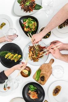 Famiglia, amici che si riuniscono per la cena. mani di persone che mangiano anatra arrosto, gnocchi, involtini primavera, tagliatelle wok, insalate, verdure, vino da bere. cena di festa di celebrazione