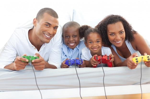 Famiglia animata che gioca video gioco sdraiato sul letto