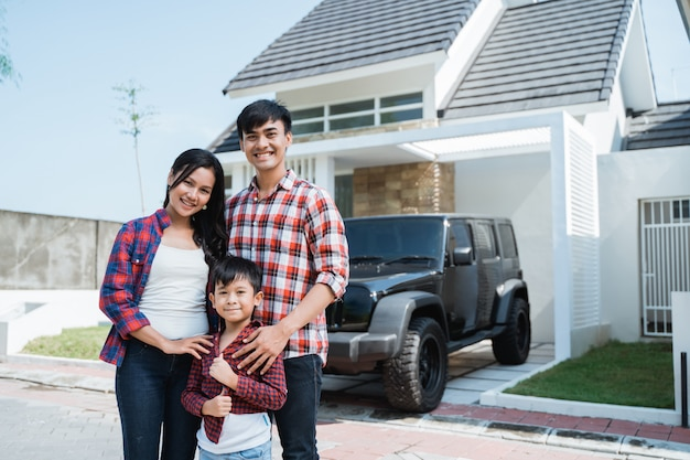 Famiglia asiatica con bambino davanti alla loro casa e auto