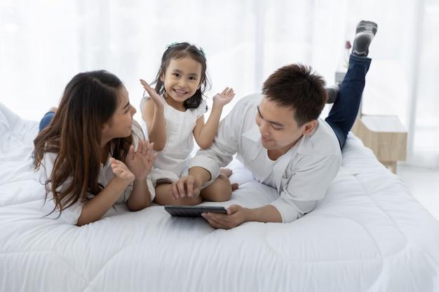 Famiglia asiatica con una tavoletta digitale