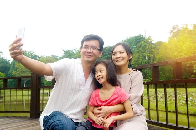Famiglia asiatica felice che prende un selfie all'aperto in un parco della città.