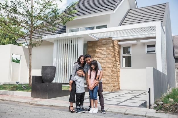 Famiglia asiatica felice davanti alla loro casa