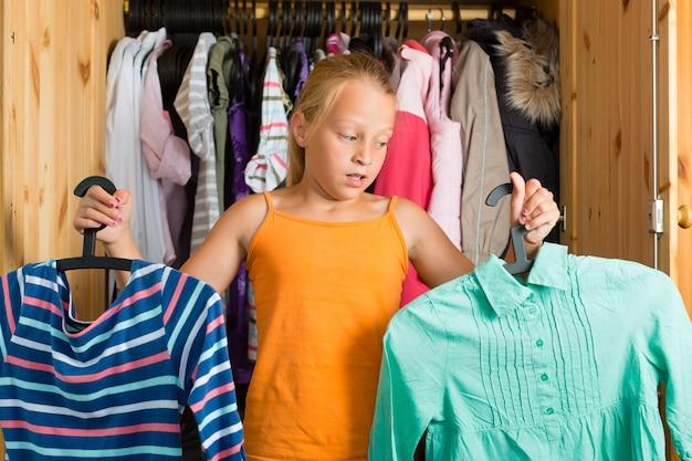 Famiglia, bambino davanti al suo armadio o guardaroba