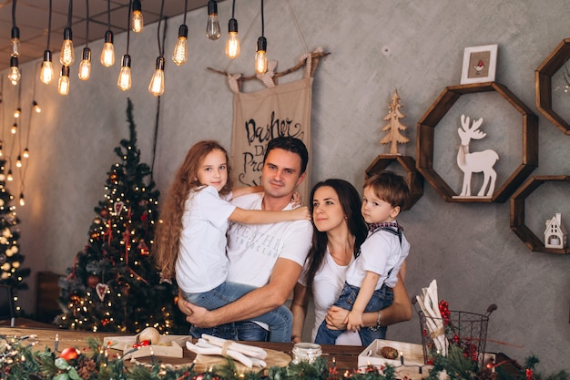 Famiglia cacasian felice alla casa per le vacanze accogliente decorata alle luci di natale. bambini e genitori allegri sono festeggiamenti tradizionali