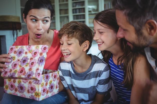Famiglia che apre il regalo di sorpresa in salone
