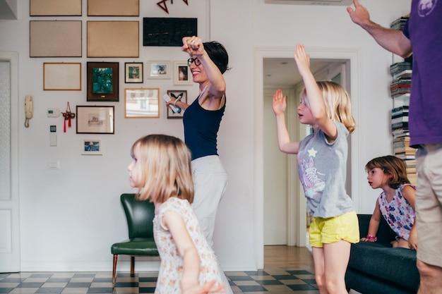 Famiglia che balla insieme al coperto giocando a videogioco