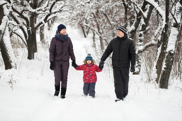 Famiglia che cammina attraverso il bosco innevato