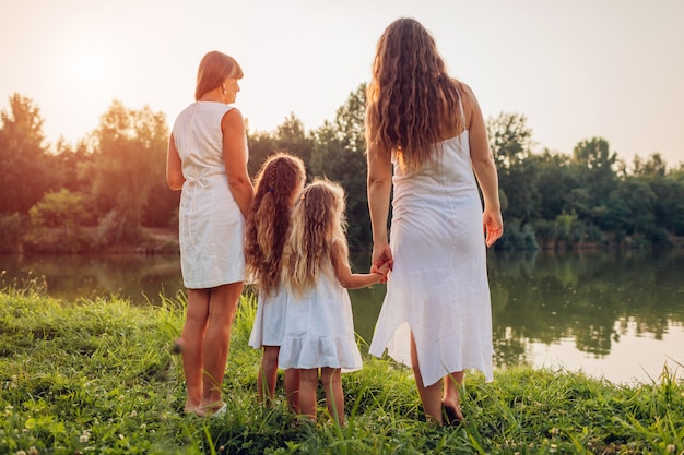 Famiglia che cammina dal fiume di estate al tramonto