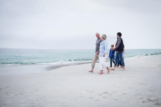 Famiglia che cammina insieme sulla spiaggia
