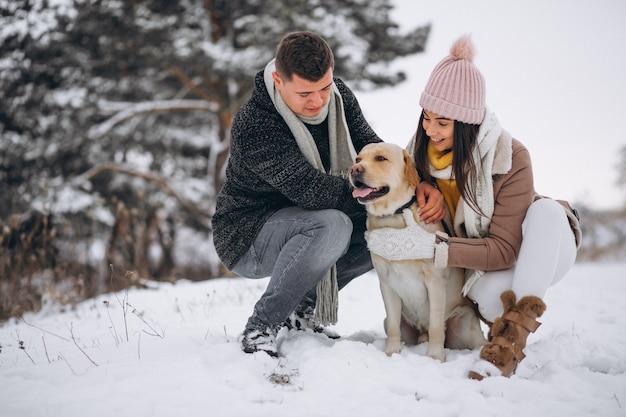 Famiglia che cammina nel parco invernale con il loro cane