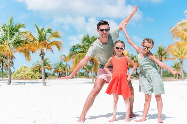 Famiglia che cammina sulla spiaggia tropicale bianca sull'isola dei caraibi