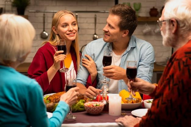 Famiglia che chiacchiera e che tiene vista frontale dei bicchieri di vino