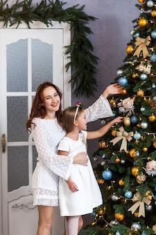 Famiglia che decora un albero di natale a casa