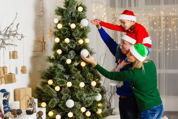 Famiglia che decora un albero di natale.