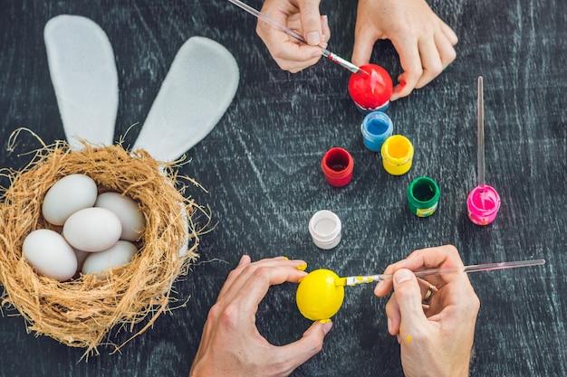 Famiglia che dipinge le uova di pasqua insieme