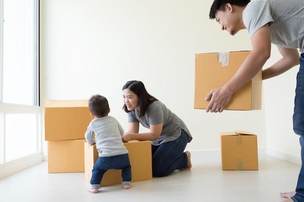 Famiglia che disimballa le scatole nella nuova casa il giorno commovente